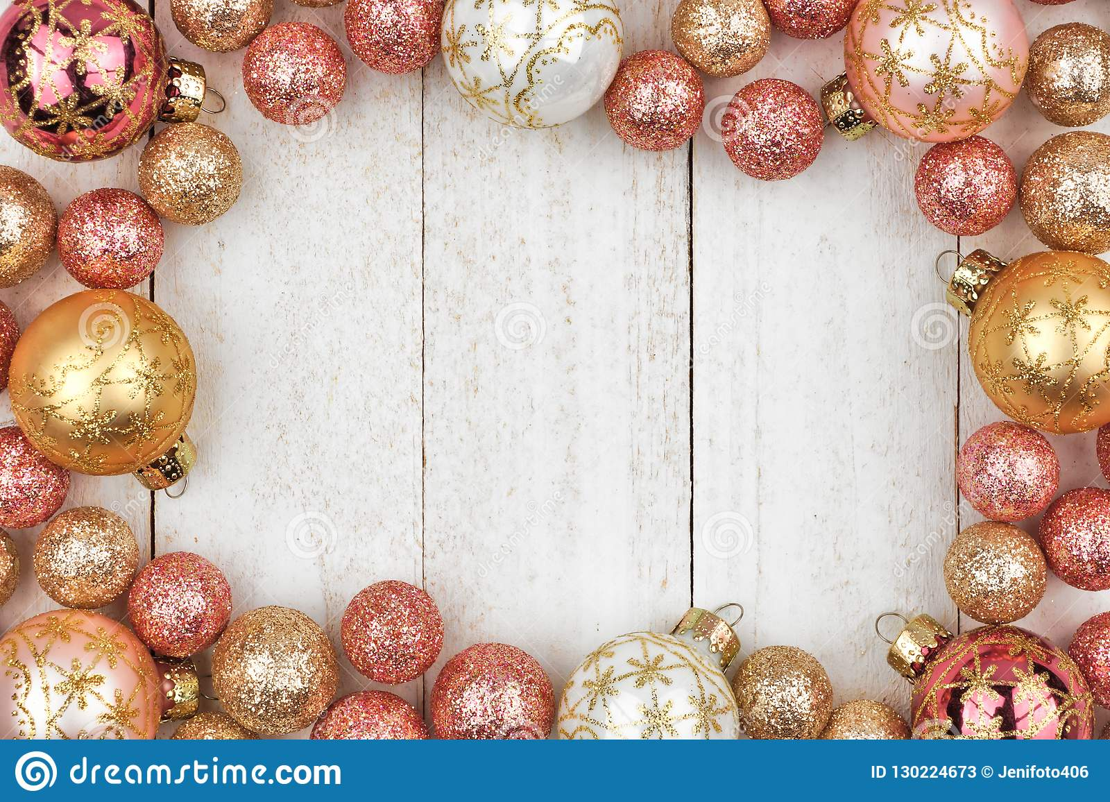 Christmas Frame Of Rose Gold And Golden Ornaments On White Wood