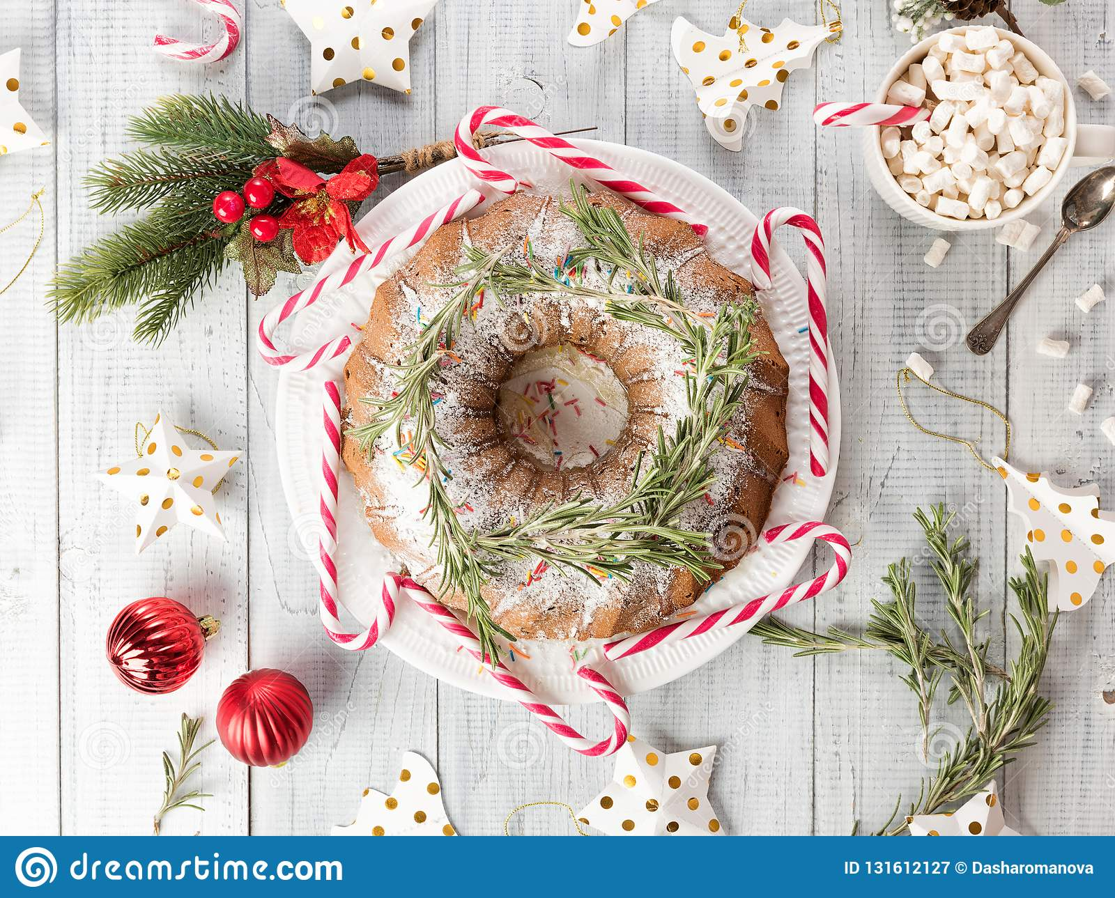 Christmas fruitcake on a white wooden table. Homemade pudding with festive decorations, candy canes