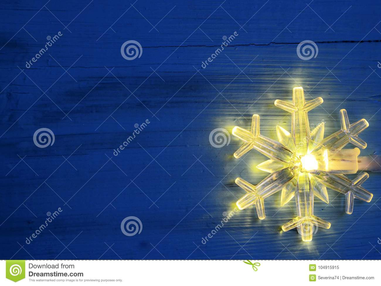 christmas garland lightsled snowflake shaped bulb on blue wooden background