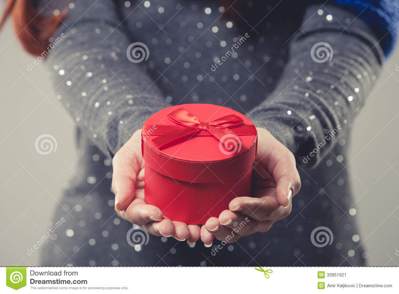 Red festive christmas gift box cradled in the cupped hands of a woman