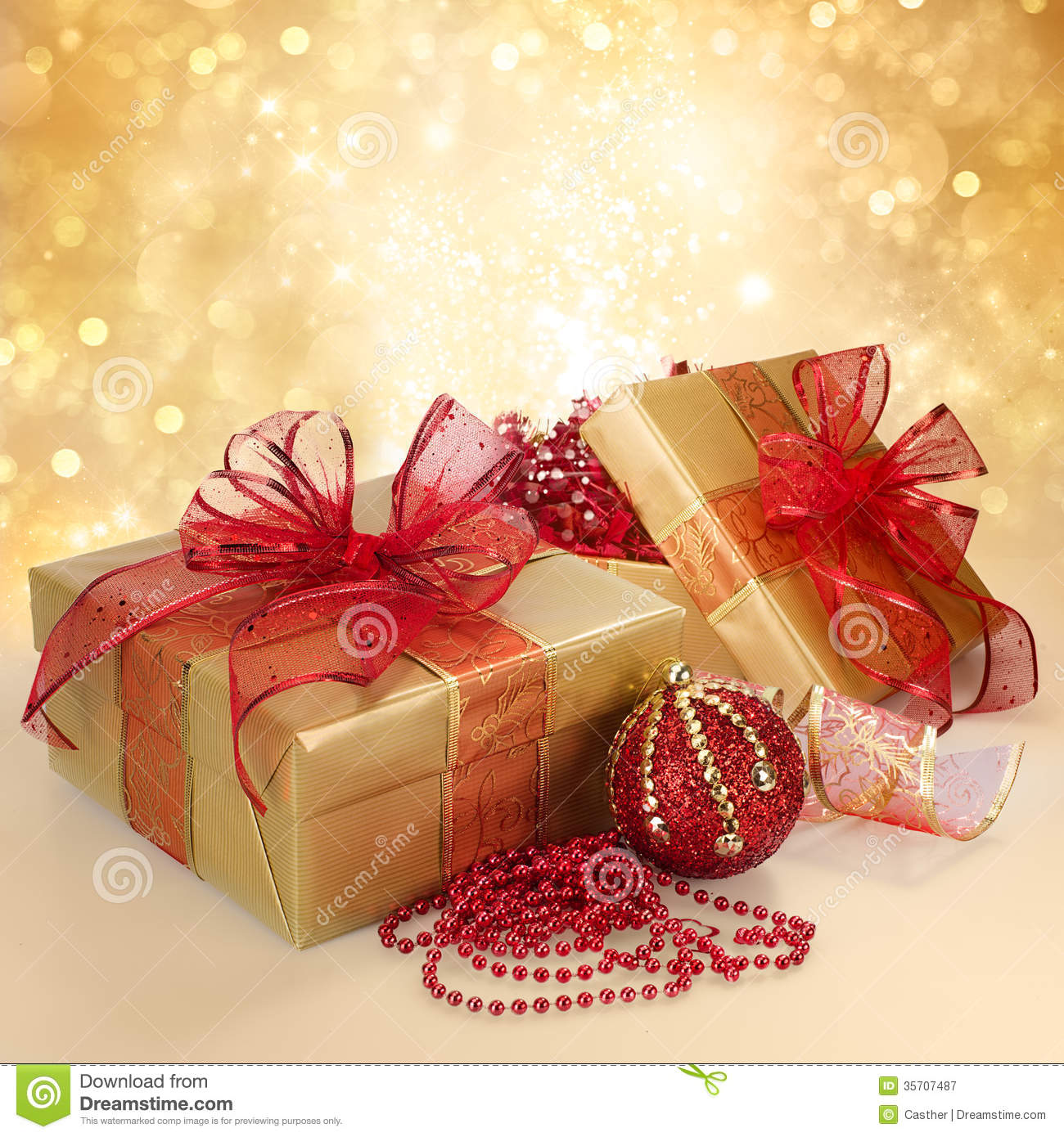 Christmas gift box and decorations in gold and red royalty free stock