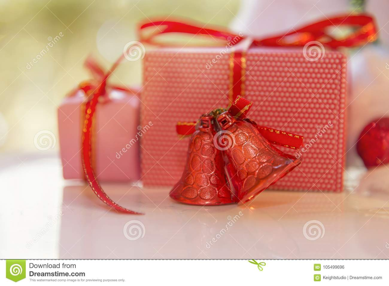 Christmas gift box, red jingle bell and blurred fir tree against