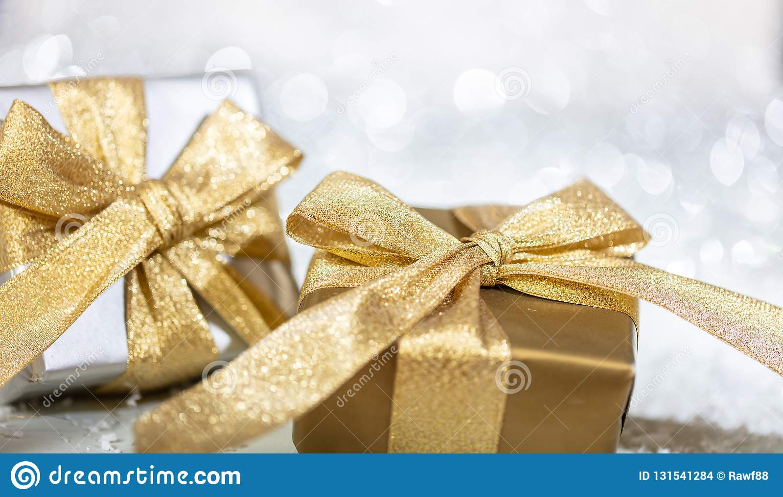 Christmas gift boxes with golden ribbons on abstract bokeh lights and glitter background