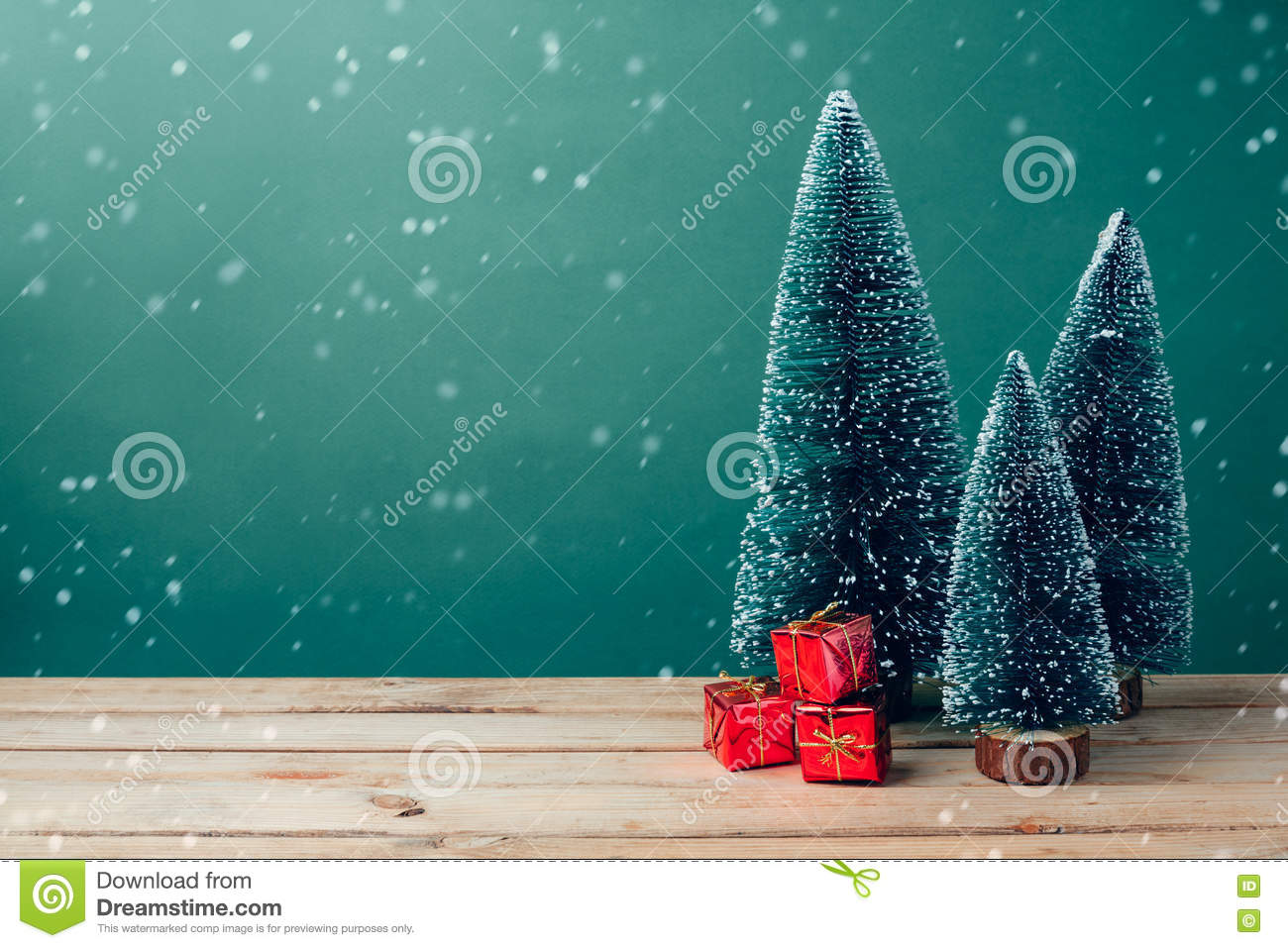 Christmas gift boxes under pine tree on wooden table over green background
