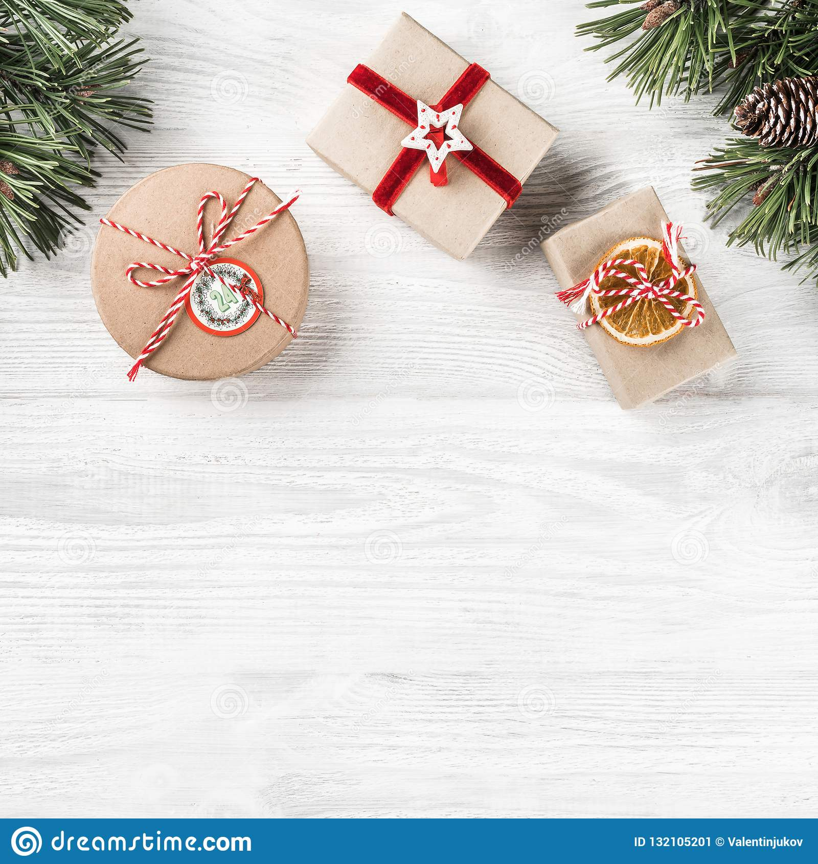 Christmas gift boxes on white wooden background with Fir branches, pine cones. Xmas and Happy New Year theme.