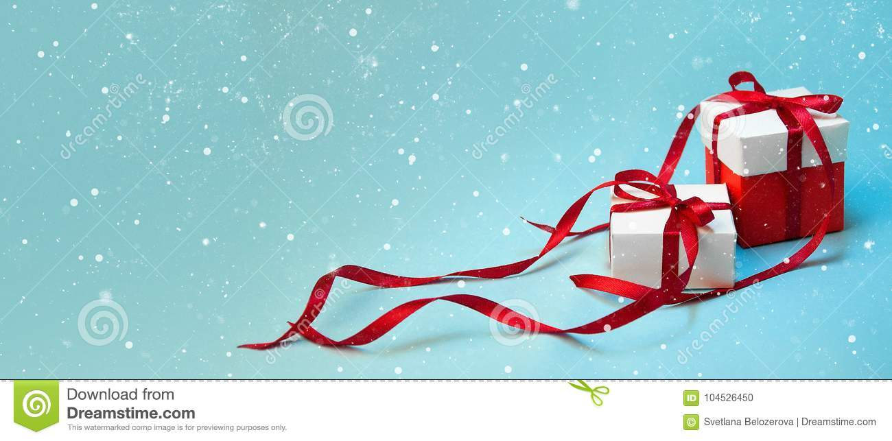 Christmas Gift`s in White Box with Red Ribbon on Light Blue Background. New Year Holiday Composition Banner. Copy Space