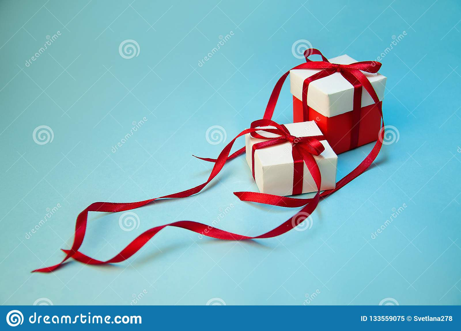 Christmas Gift`s in White Box with Red Ribbon on Light Blue Background. New Year Holiday Composition. Copy Space