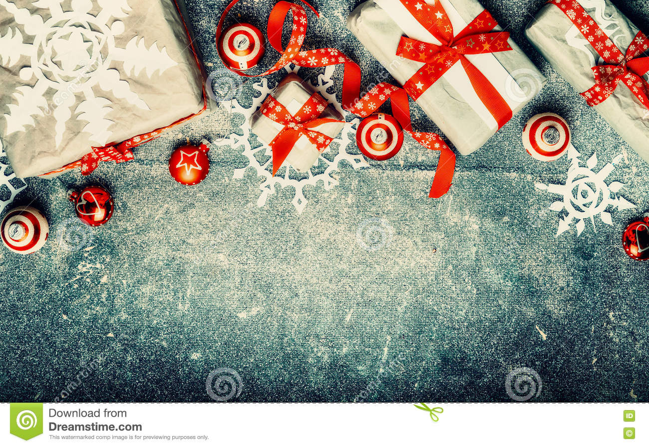 Christmas gifts, red festive holiday decorations and paper snowflakes on vintage background, top view