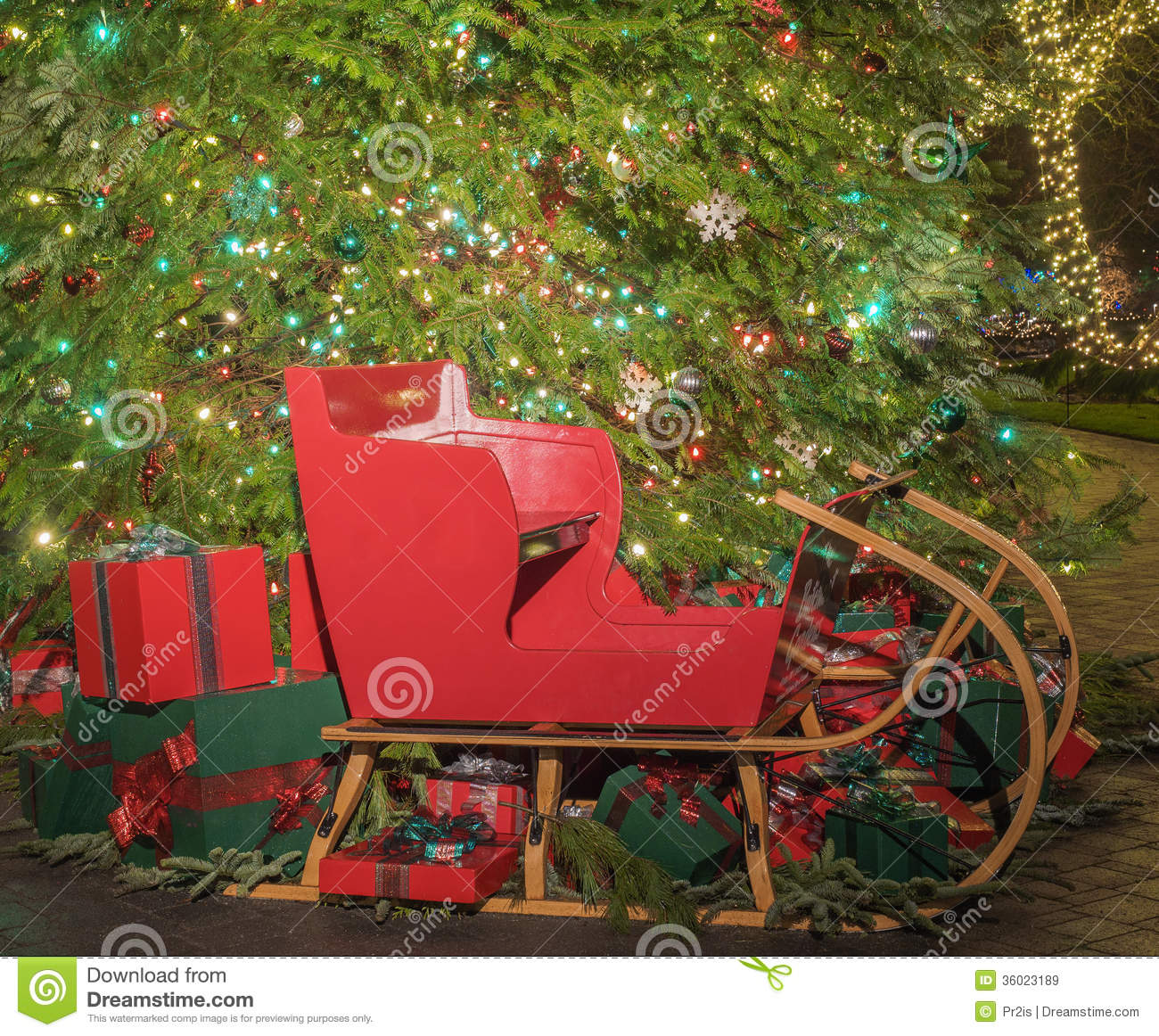 Christmas Gifts And Sled Under The Tree Royalty Free Stock