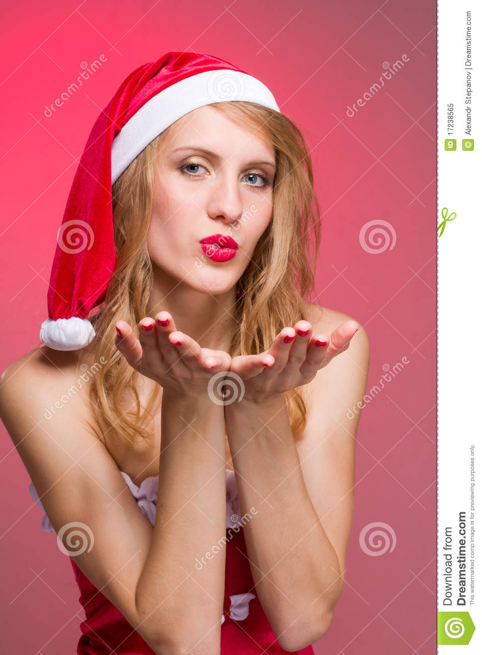 Christmas girl wearing santa claus clothes blowing on a red background