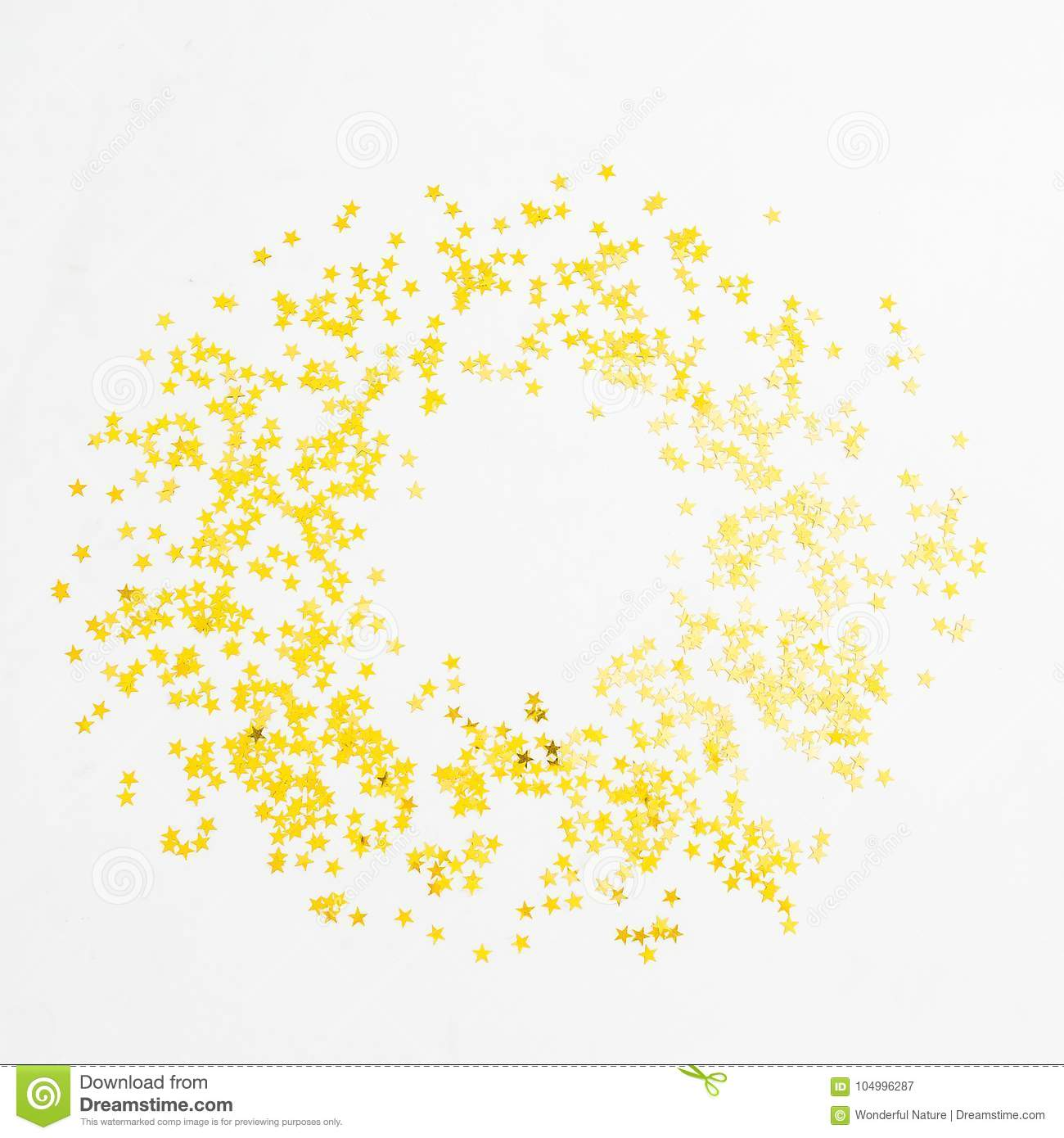 Christmas golden confetti on white background. Round frame. Flat lay, top view