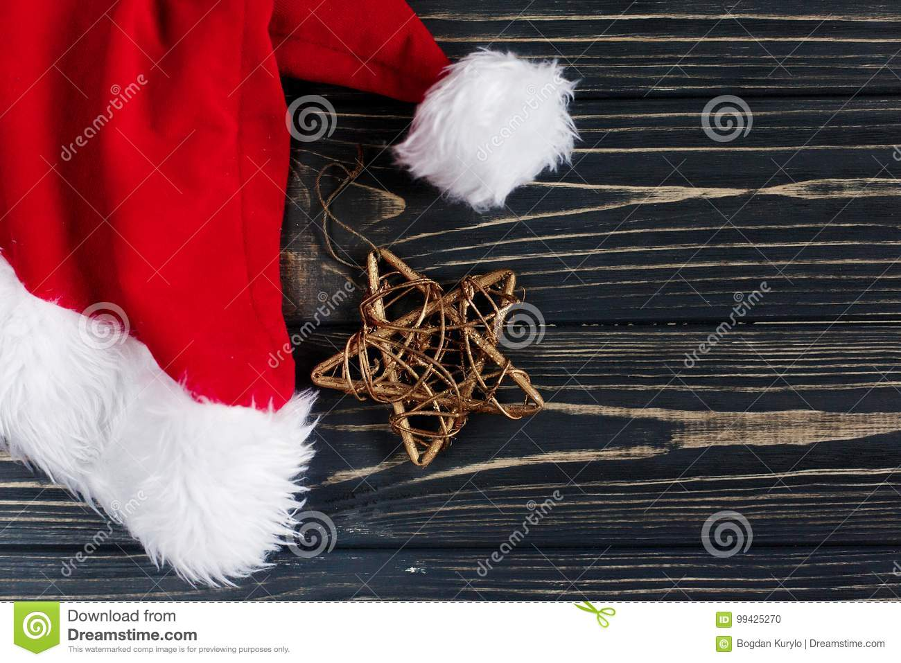 7e20c5bad84f5 Christmas golden star and santa hat on stylish black rustic wooden  background. space for text. holiday greeting card concept. unusual creative  top view