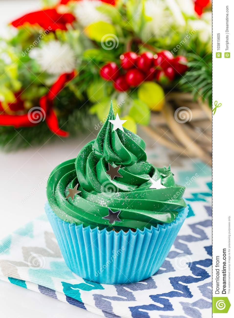 christmas green cupcake with star sprinkles in blue cup on white background with festive decorations