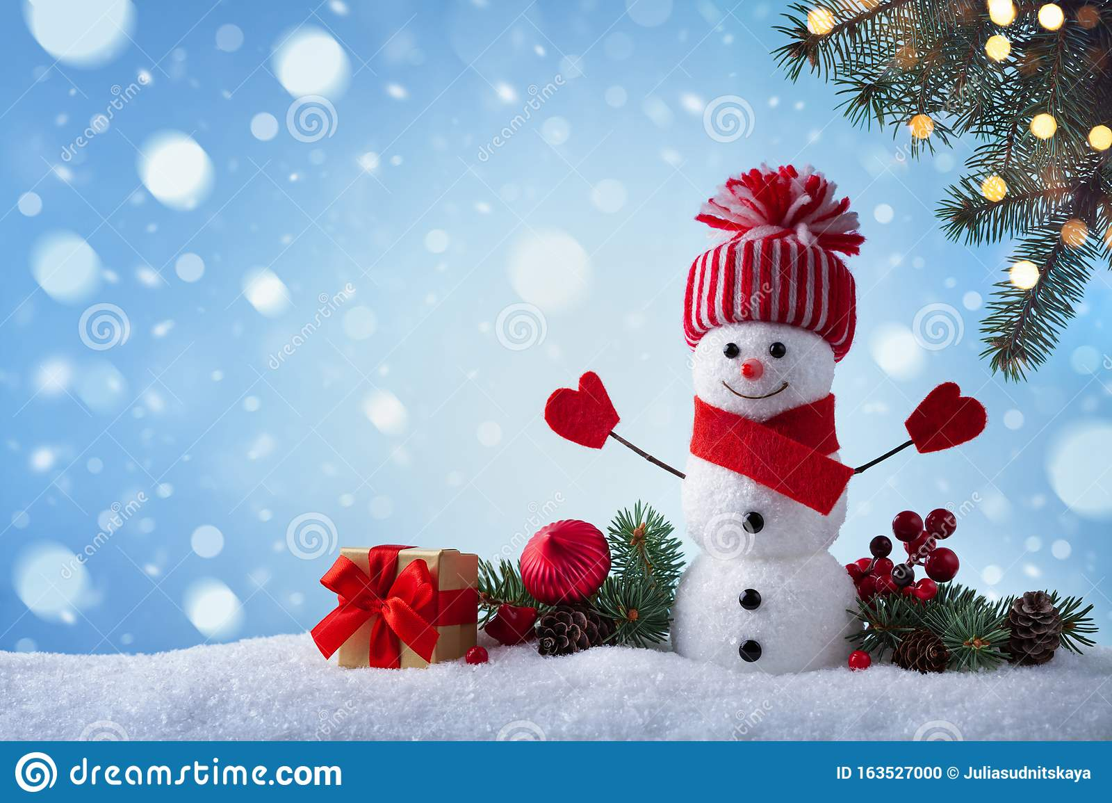 Christmas greeting card with funny snowman, gift box and fir tree branches in winter scenery. Snowy background
