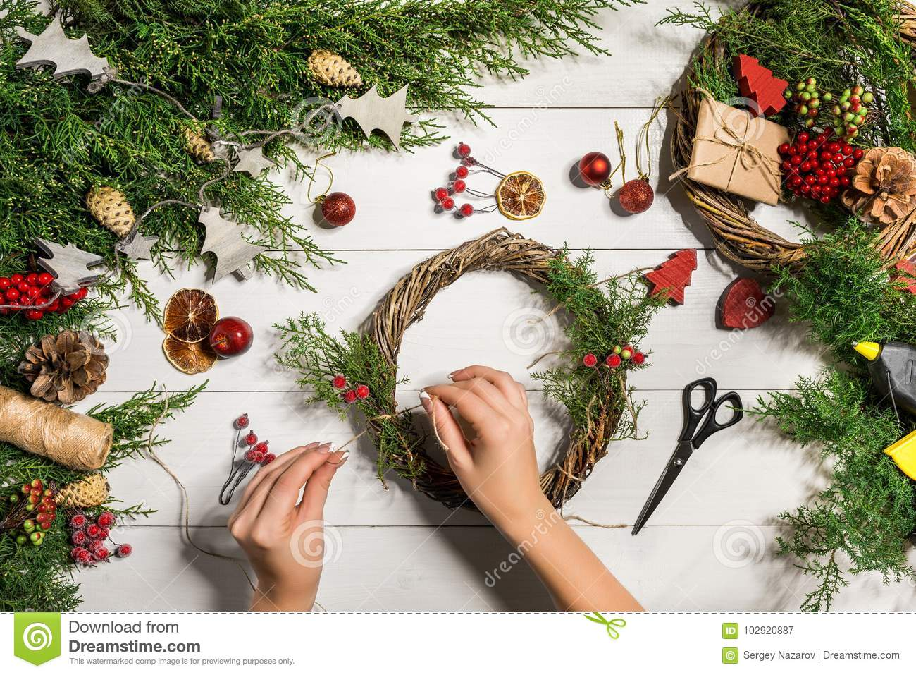 Christmas handmade diy background. Making craft xmas wreath and ornaments. Top view of white wooden table with female