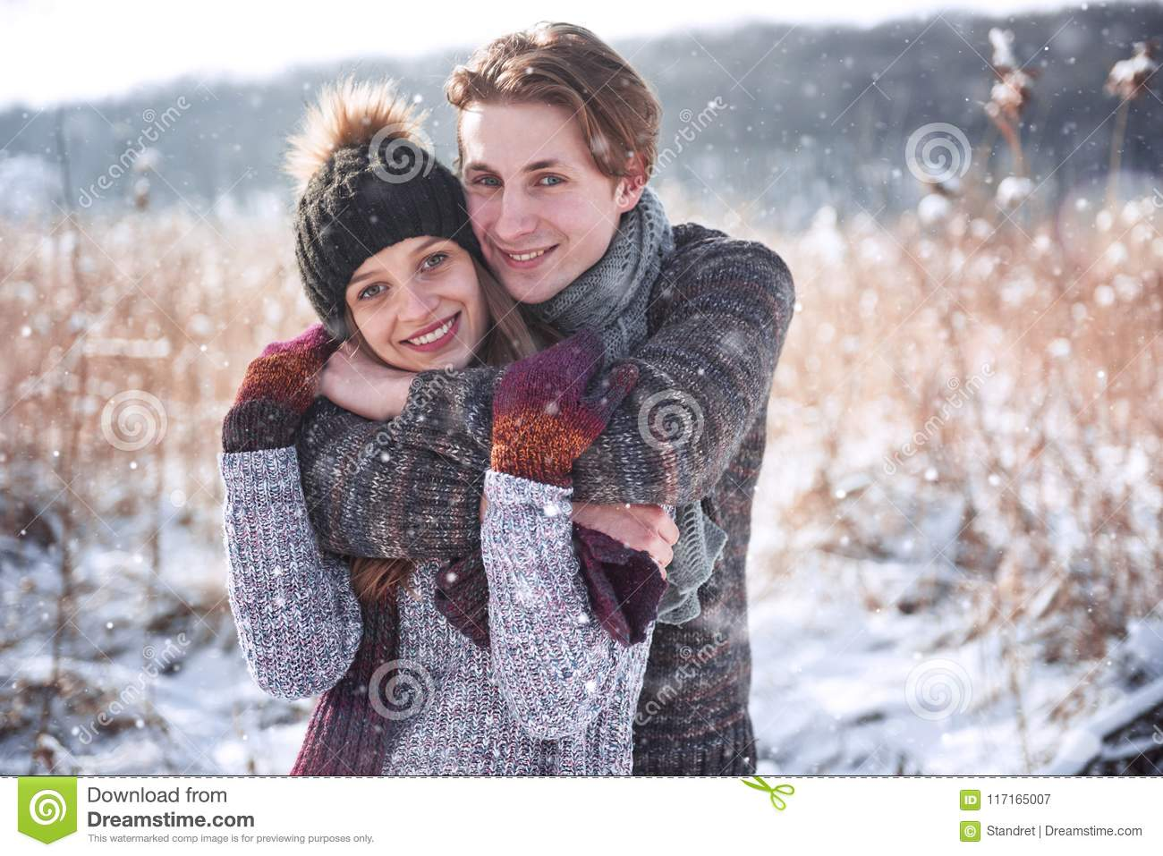 Christmas happy couple in love embrace in snowy winter cold forest, copy space, new year party celebration, holiday and