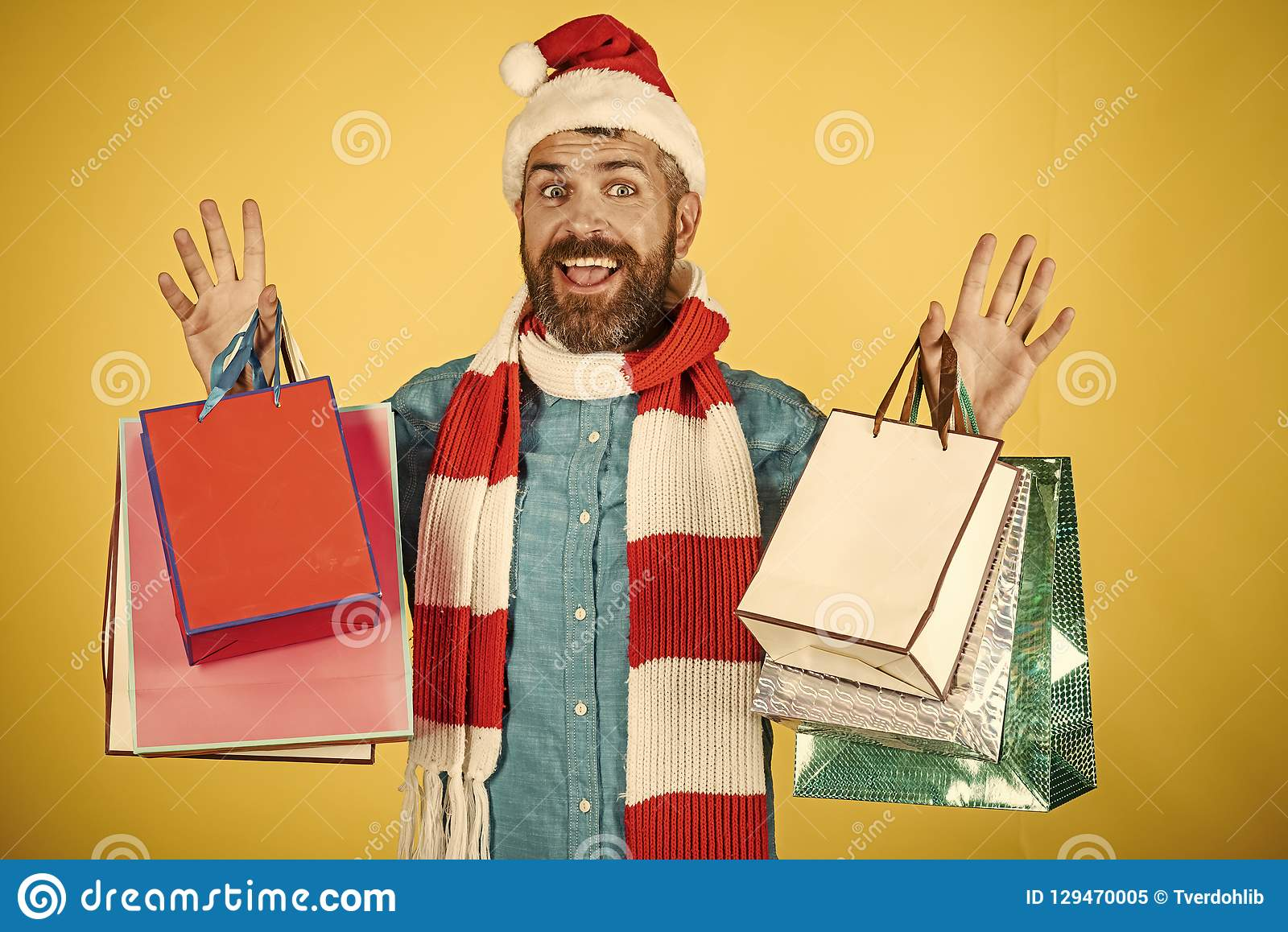64fdab60958f7 Christmas hipster shopper smile in santa hat and scarf. Man hold shopping  bags on yellow background. New year