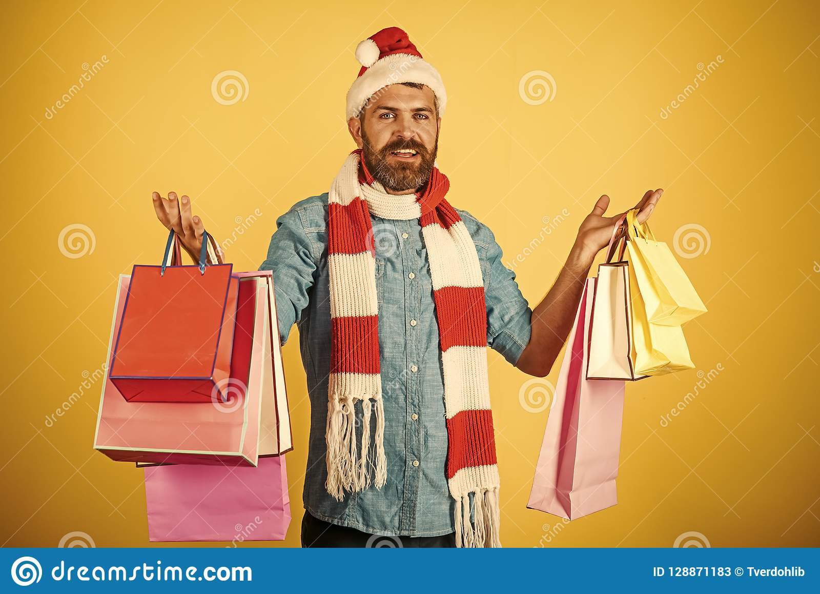 e1814d3ae7657 Christmas hipster shopper wear santa hat and scarf. Black friday sale  concept. Man hold shopping bags on yellow background. New year