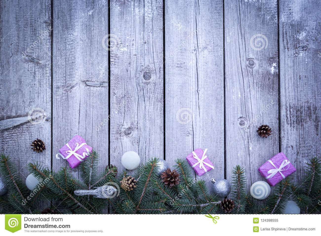 Christmas holiday background with gifts boxes with fir branches, pine cones, christmas balls on wooden table. Flat lay, top view w