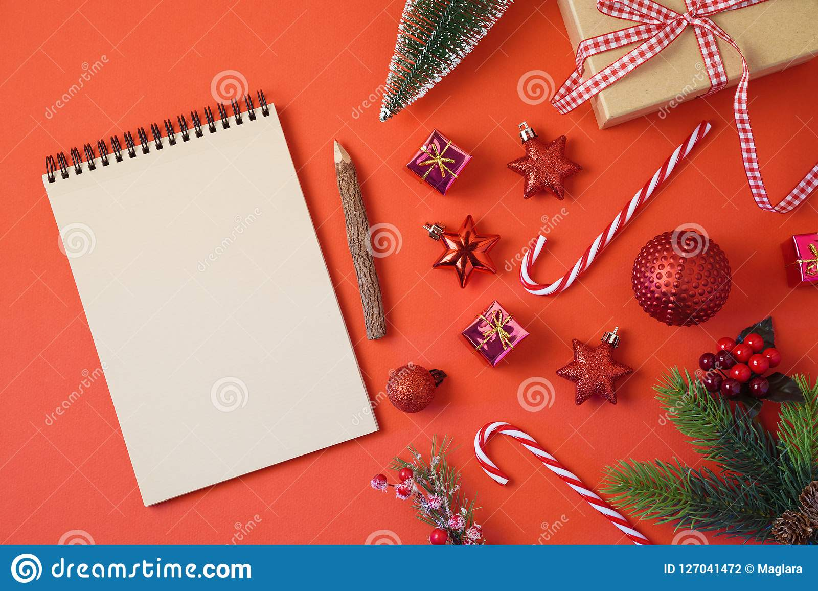 Christmas holiday background with notebook and decorations on red table.
