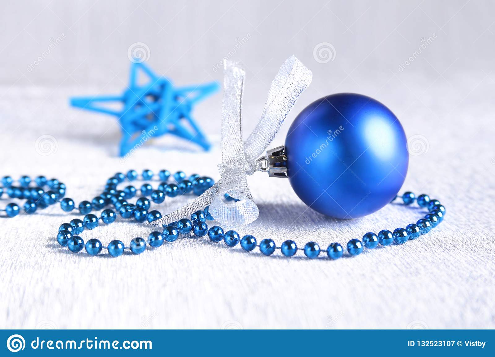 Christmas or holiday composition with blue silver balls on billowy feathers with snow and snowflakes.