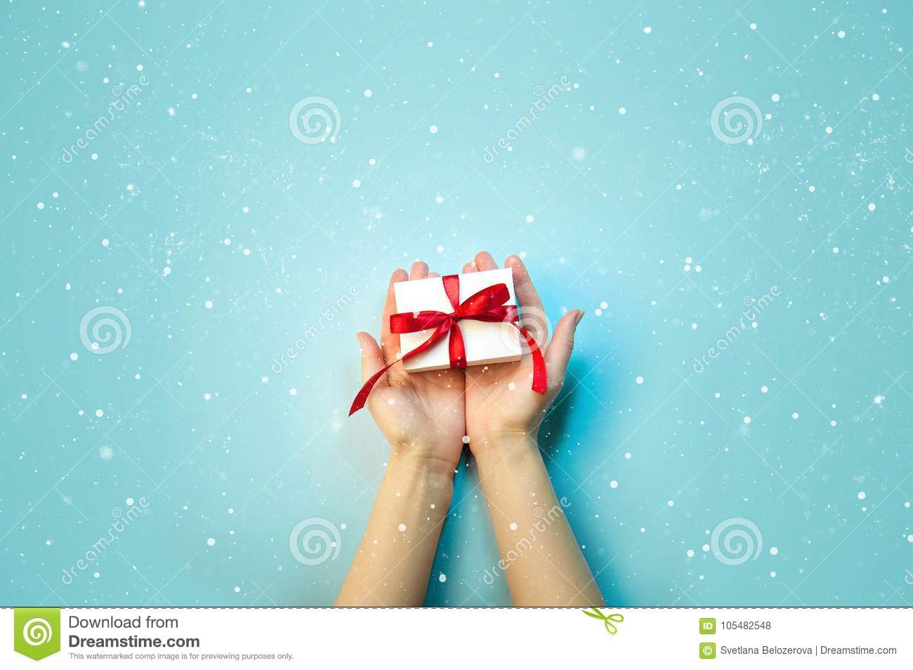 Christmas Holiday Composition. New Year Gift in White Box with Red Ribbon in Female Hands on Light Blue Background Flat Lay Top Vi
