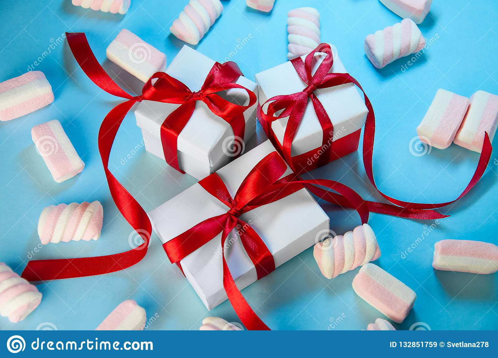 Christmas Holiday Composition. New Year Gift White Boxes Red Ribbon with Marshmallows on Blue Background. Flat Lay