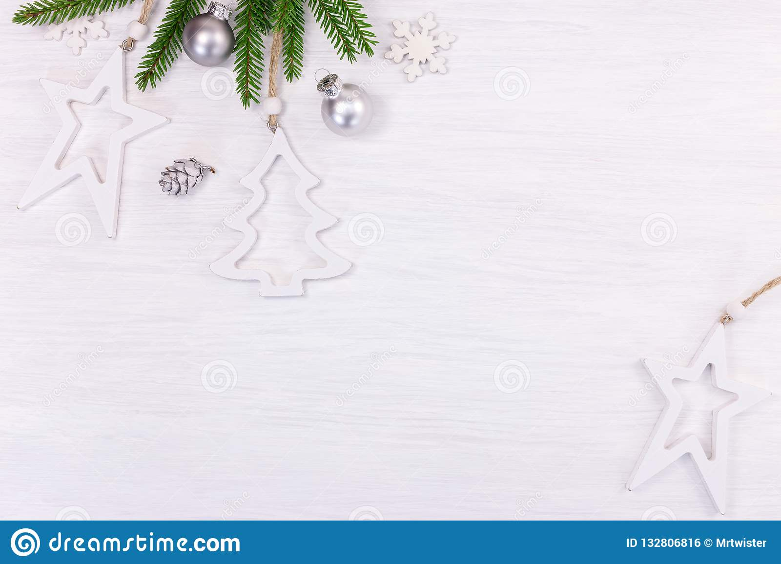 christmas holidays background with green fir tree branch, decorative silver balls and white wooden stars