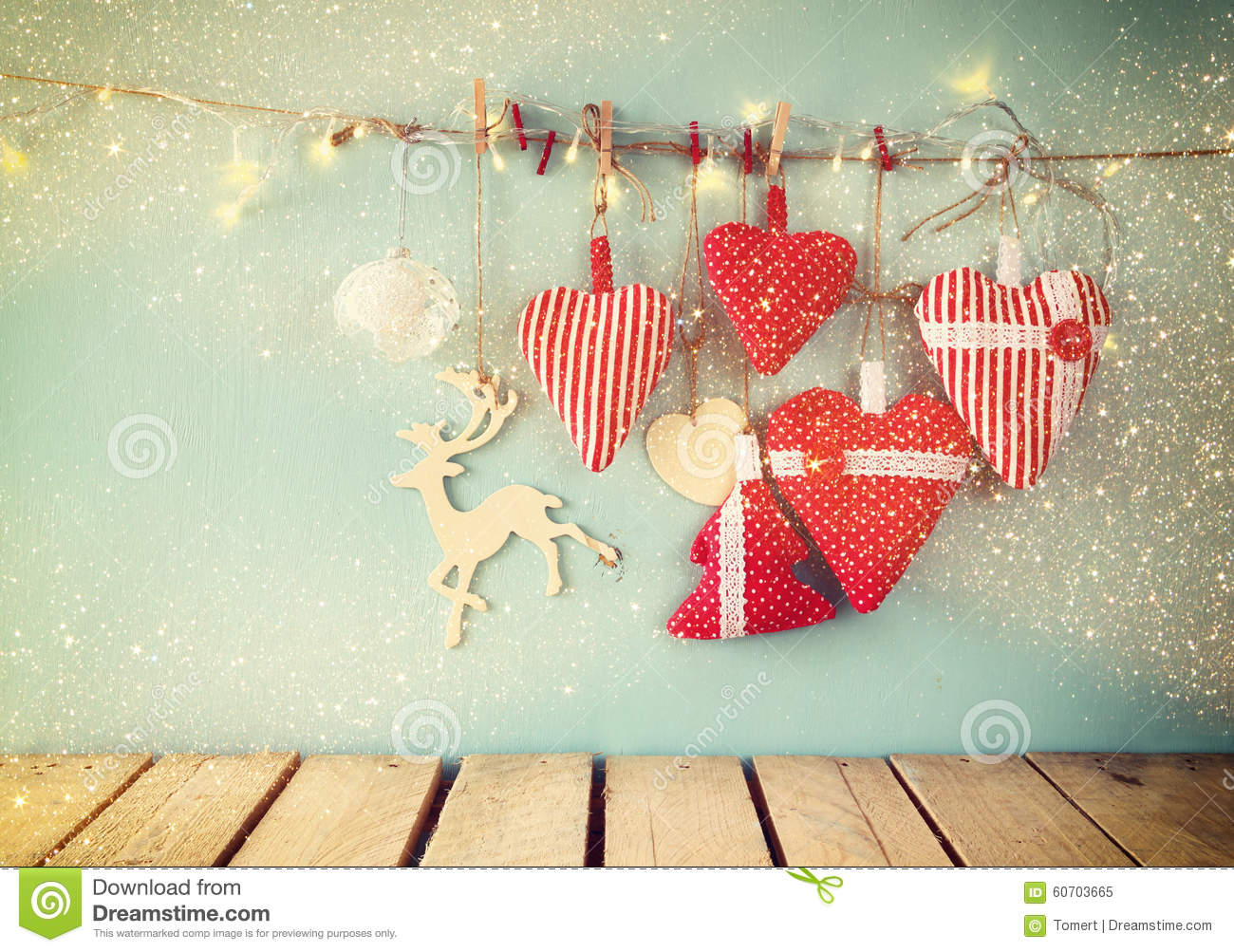 Christmas image of fabric red hearts and tree. wooden reindeer and garland lights, hanging on rope