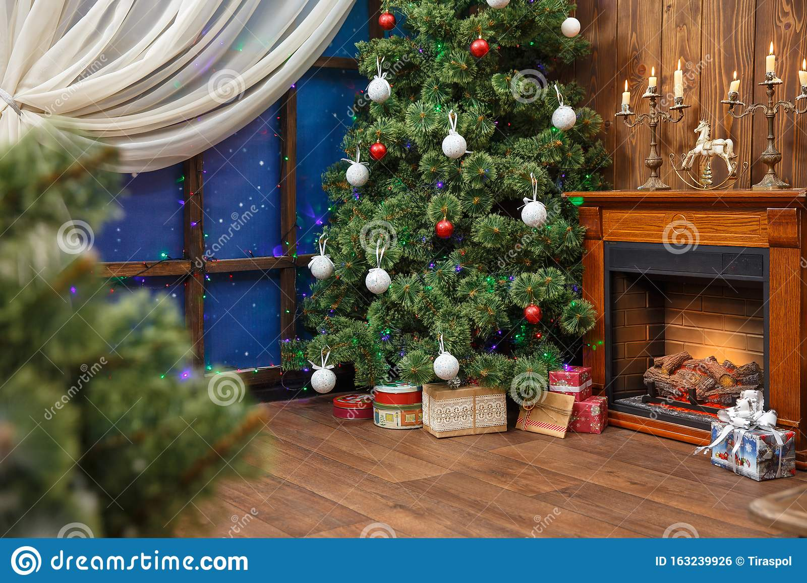 Christmas Interior With Toys And Lots Of Candles Wooden Fake Fireplace Christmas Tree Boxes In Studio Stock Photo Image Of Decor Nobody 163239926