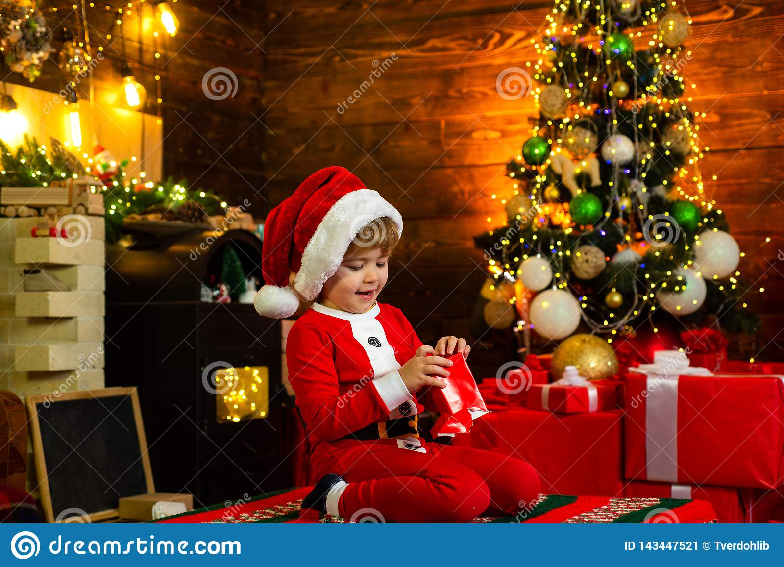 Christmas Kids. Happy little kid is wearing Santa clothes, playing with Christmas gift box. Fireplace background