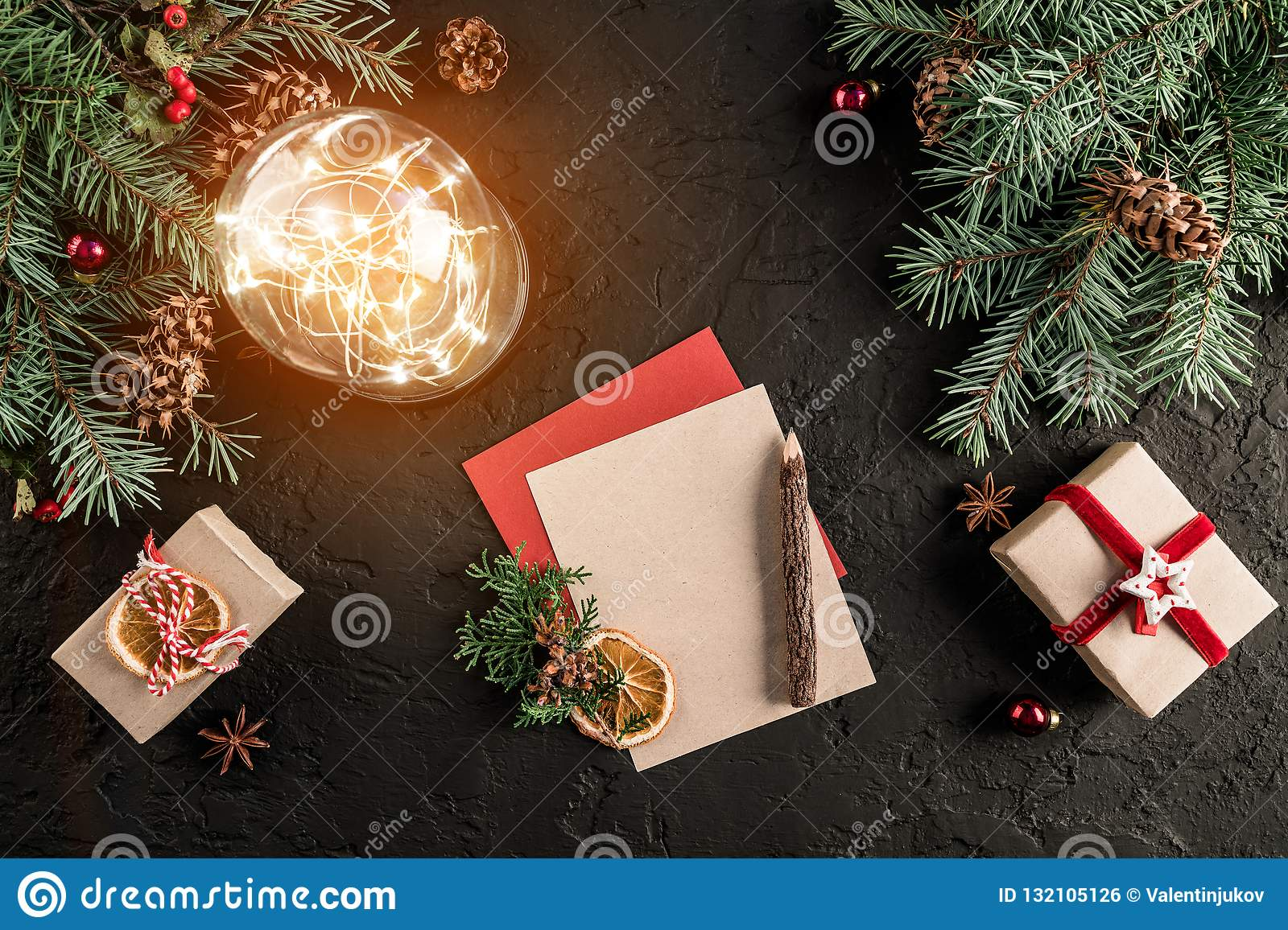 Christmas letter for Santa on dark background with gifts, fir branches, pine cones, glowing ball. Xmas and Happy New Year theme.