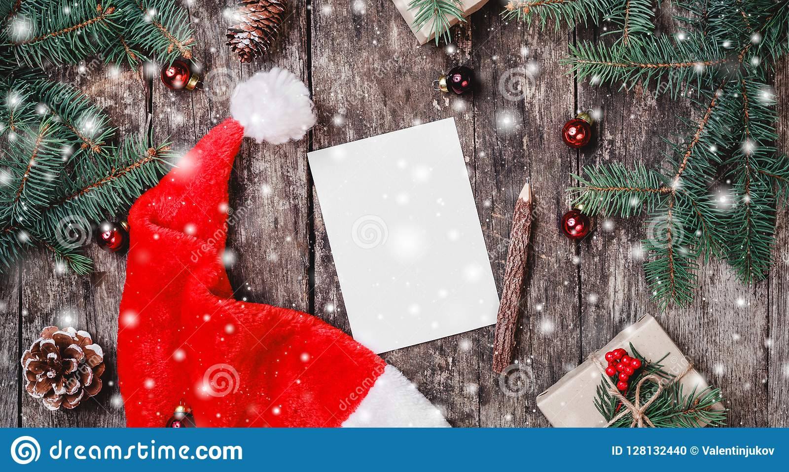 Christmas letter on wooden background with red Santa hat, Fir branches, pine cones, red decorations. Xmas and Happy New Year