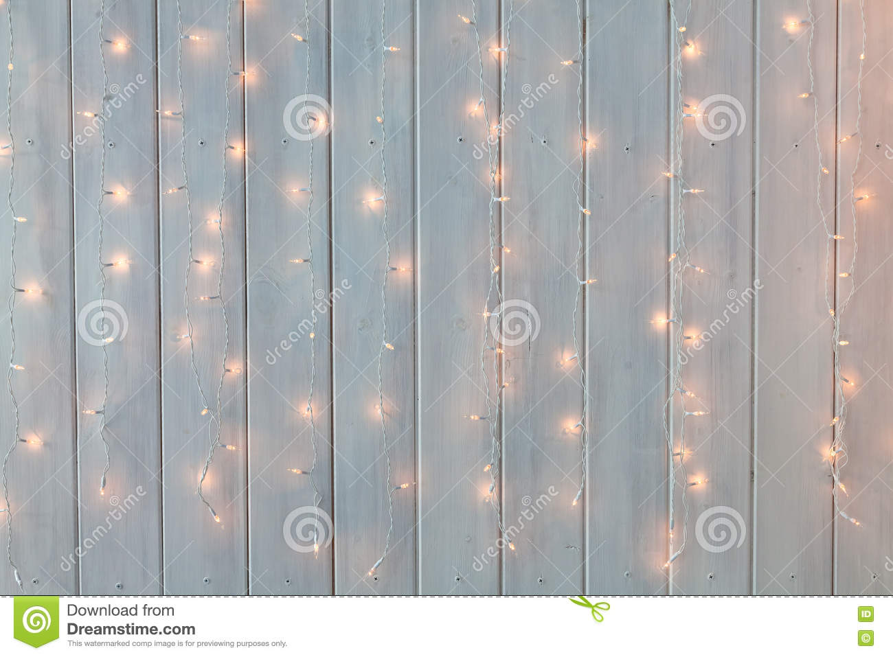 Christmas lights burning on a white wooden background. New Year back.