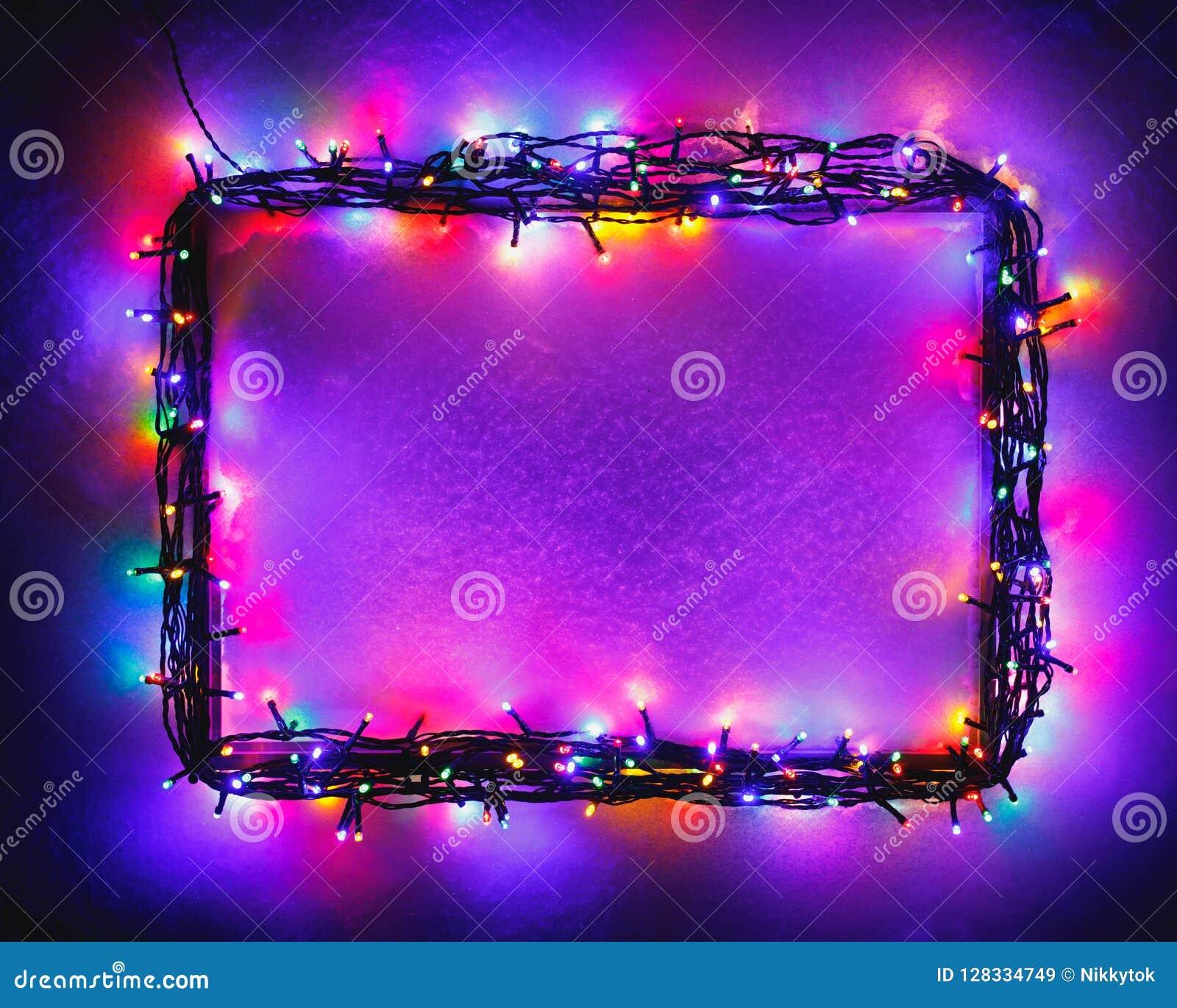Christmas lights frame on snow background, purple color