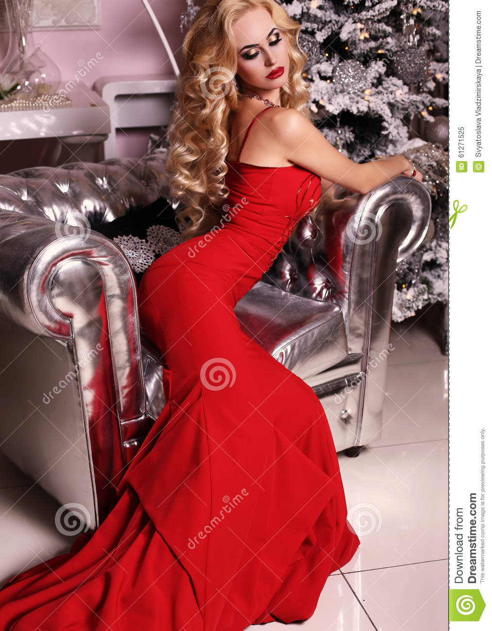 fashion interior photo of beautiful gorgeous woman with blond hair in luxurious dress posing in room with christmas tree and decorations
