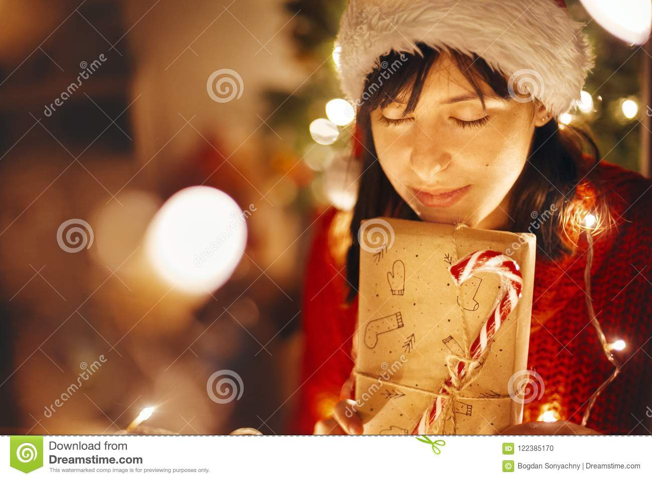 3e35d344553f3 Christmas magic moments. girl in santa hat and red sweater holding christmas  present in lights in evening festive room at tree illumination. merry  christmas ...