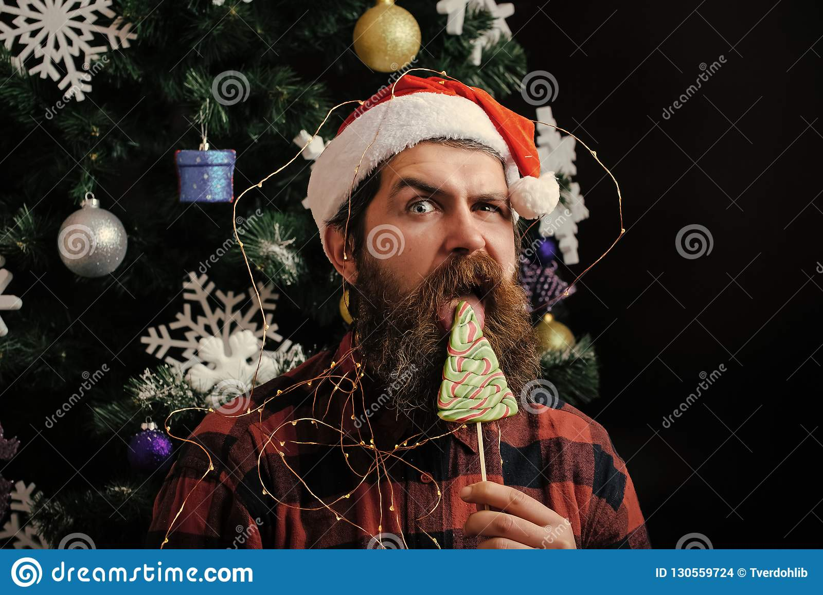 Christmas man with beard on surprised face and lollipop.