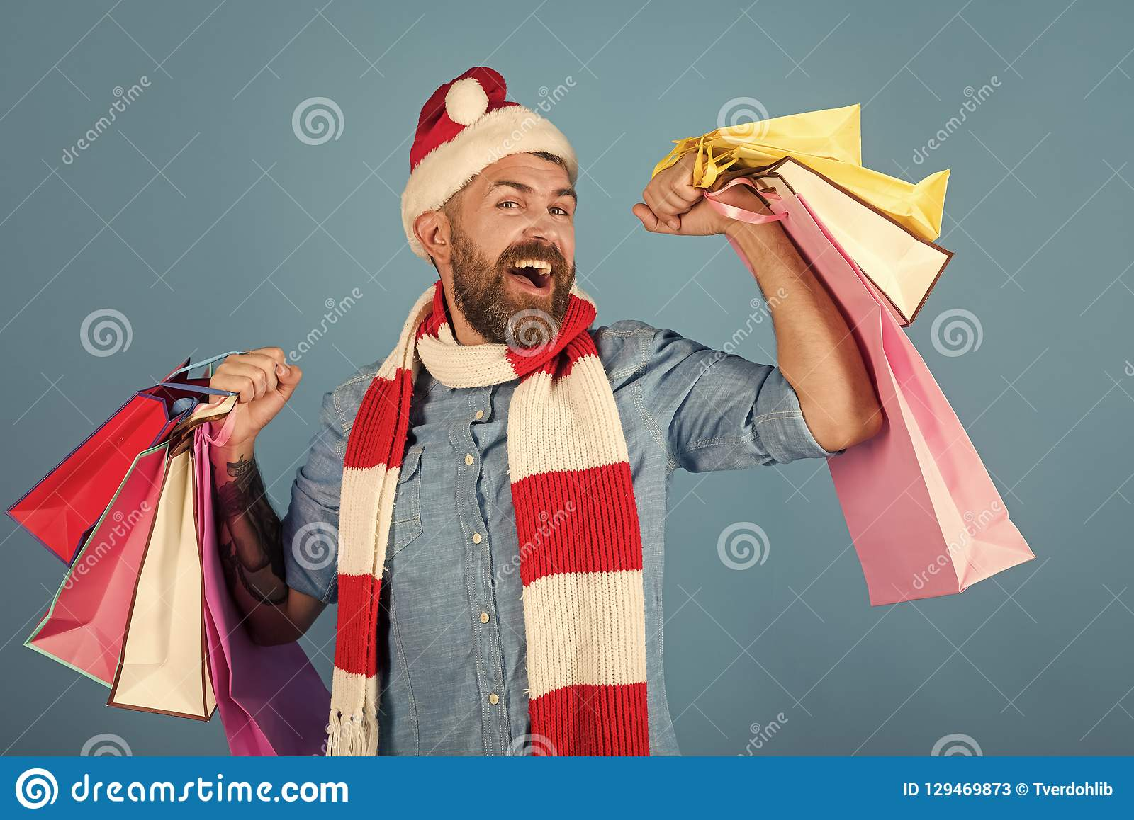 71e30d5084d3c Christmas man shopper happy smile in santa hat and scarf. Hipster hold  shopping bags on blue background. Winter holidays celebration. New year ...