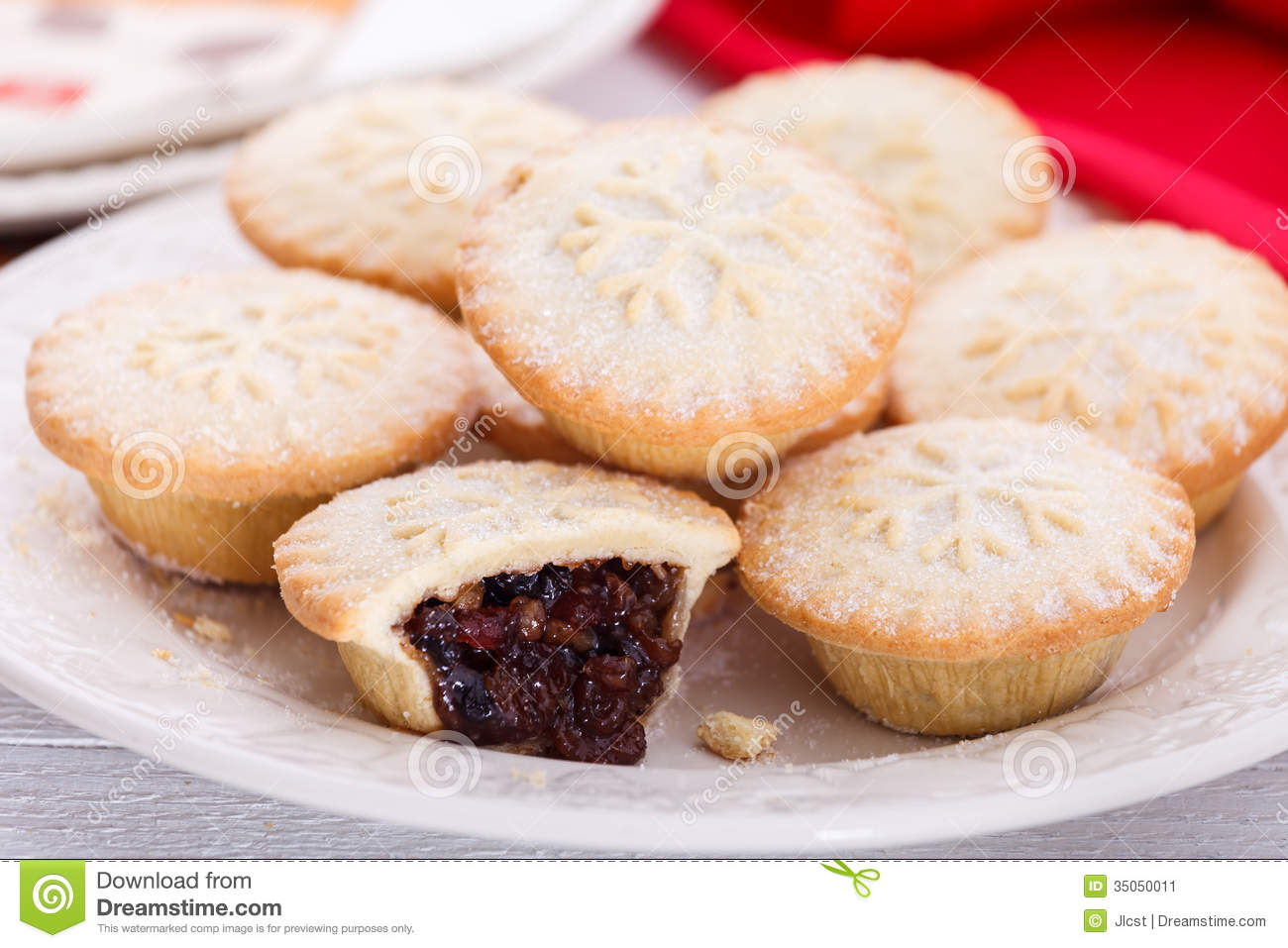Sweet and spicy Christmas mince pies stacked on white plate.