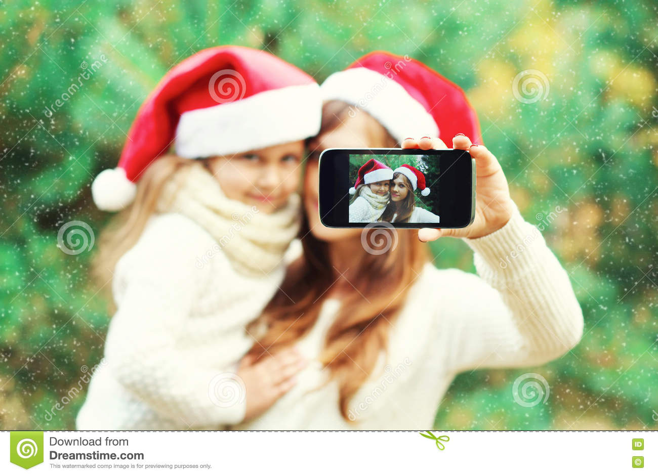 Christmas mother and child taking picture self portrait on smartphone together, closeup, blurred background