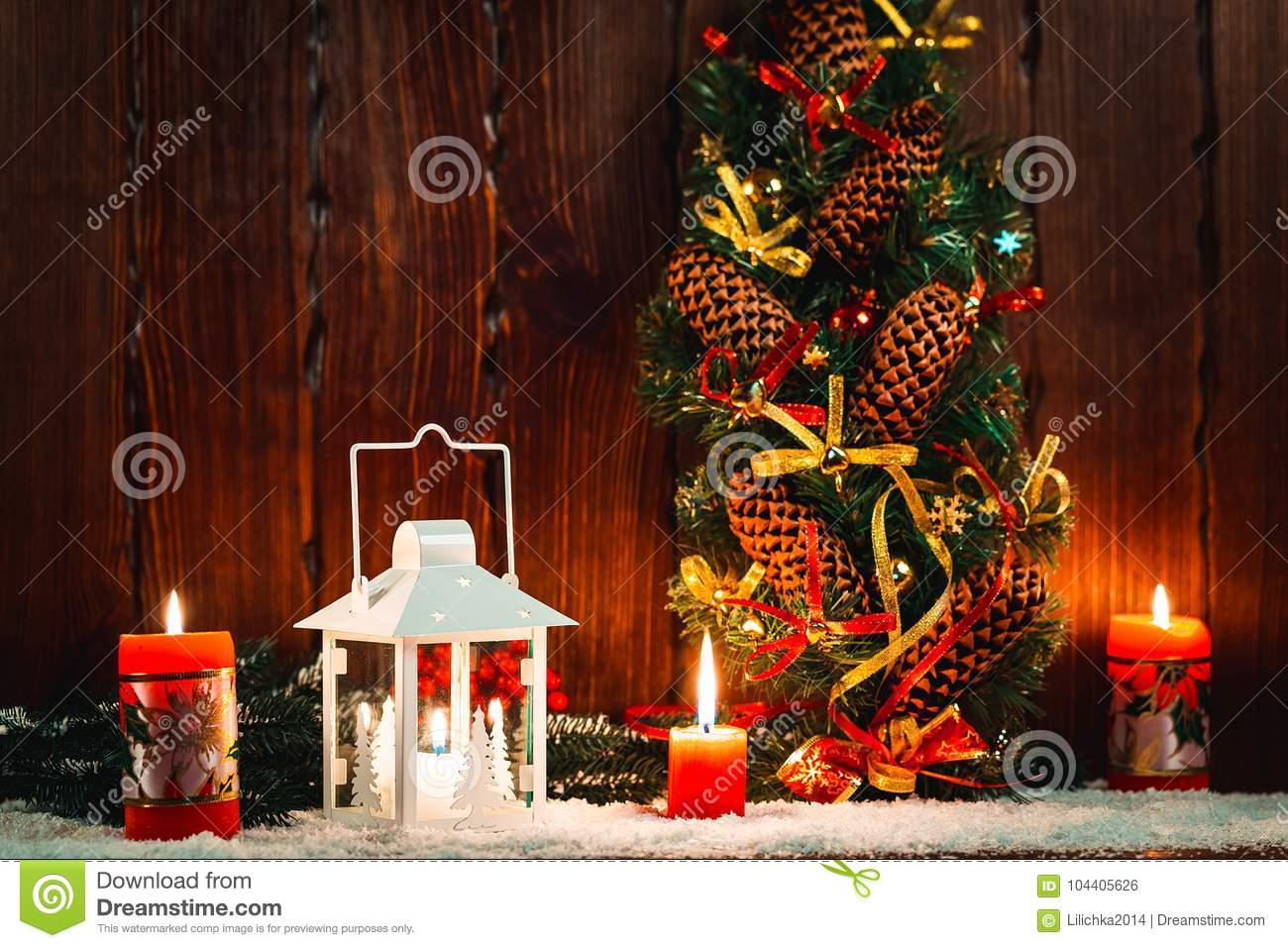 christmas and new year background with christmas candle lantern and christmas tree branches snow and