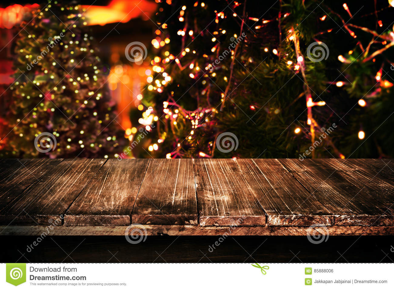 Christmas and New year background with empty dark wooden deck table over christmas tree and blurred light bokeh