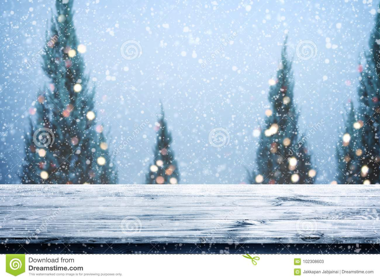 christmas and new year background with wooden deck table over christmas tree