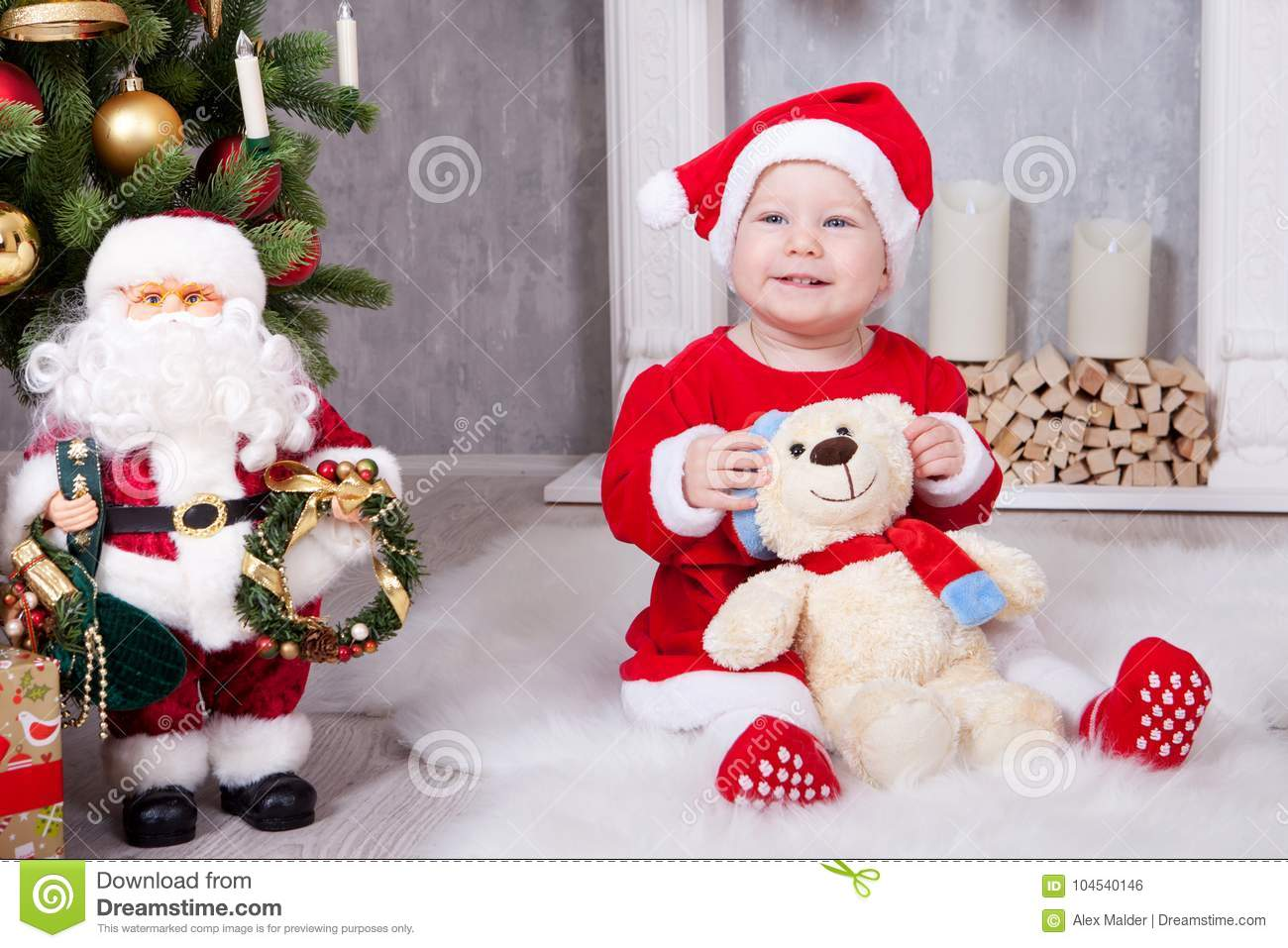 Christmas or New year celebration. Little girl in red dress and santa hat with bear toy sitting on the floor near the Christmas tr