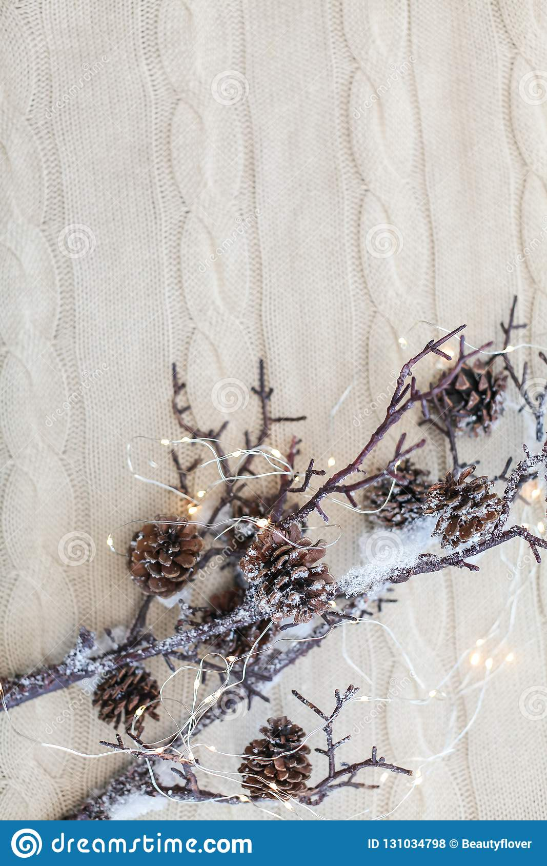 Christmas and New Year composition. Close up snow branches with cones and garland on knitted white background.