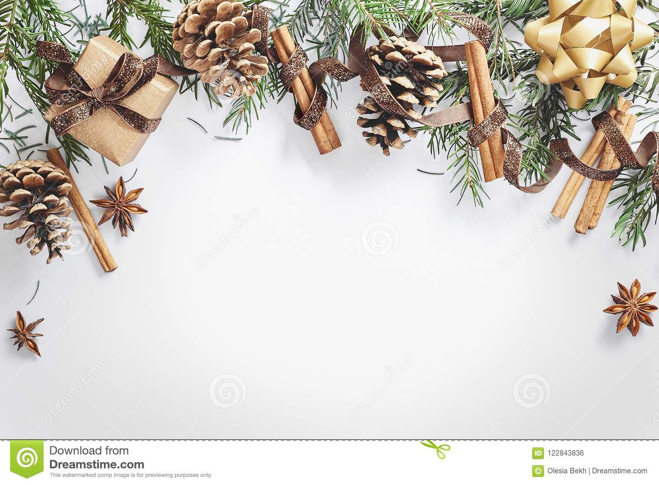 Christmas and New Year composition. Gift box with ribbon, fir branches with cones, star anise, cinnamon on white background