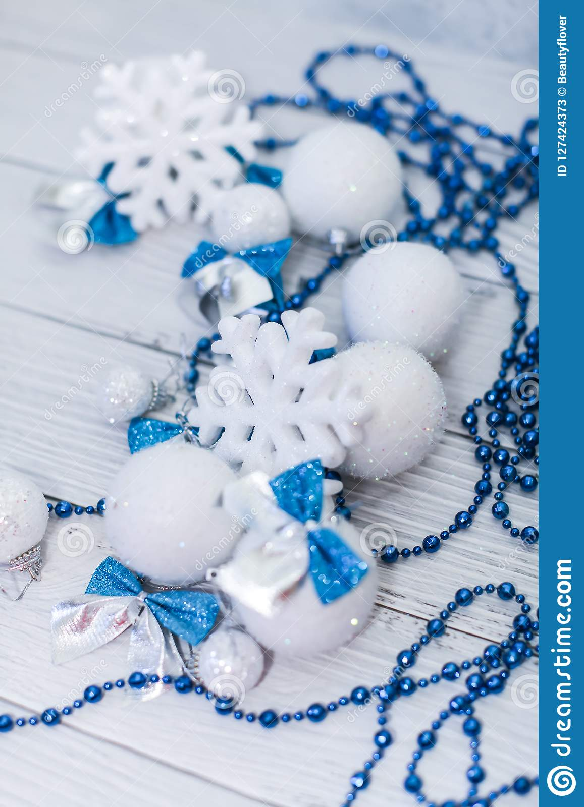 Christmas or new year composition in silver white and blue colors with balls snowflake bows and beads on white wood