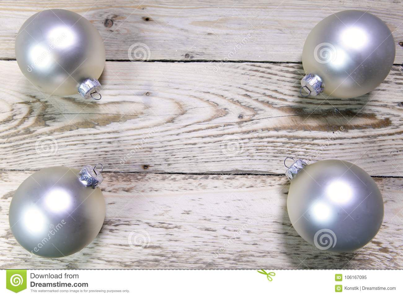 Christmas and New Year Concept. Four nacreous silvery New Year`s balls on corners of wooden board, Top view, flat lay