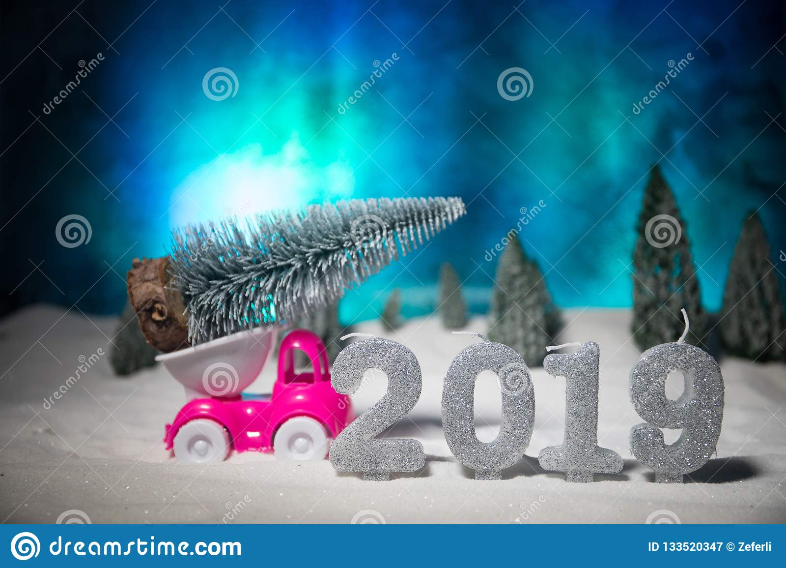 Christmas or New Year concept. Toy car carrying a Christmas tree through the forest in snowfall. Holiday decorated background